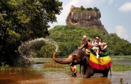 A tame elephant sprays water at foreign tourists during a safari ride in Sigiriya, about 100 kilometers (62 miles), north east of Colombo, Sri Lanka, Friday, Dec. 2, 2011. (AP Photo/Gemunu Amarasinghe)